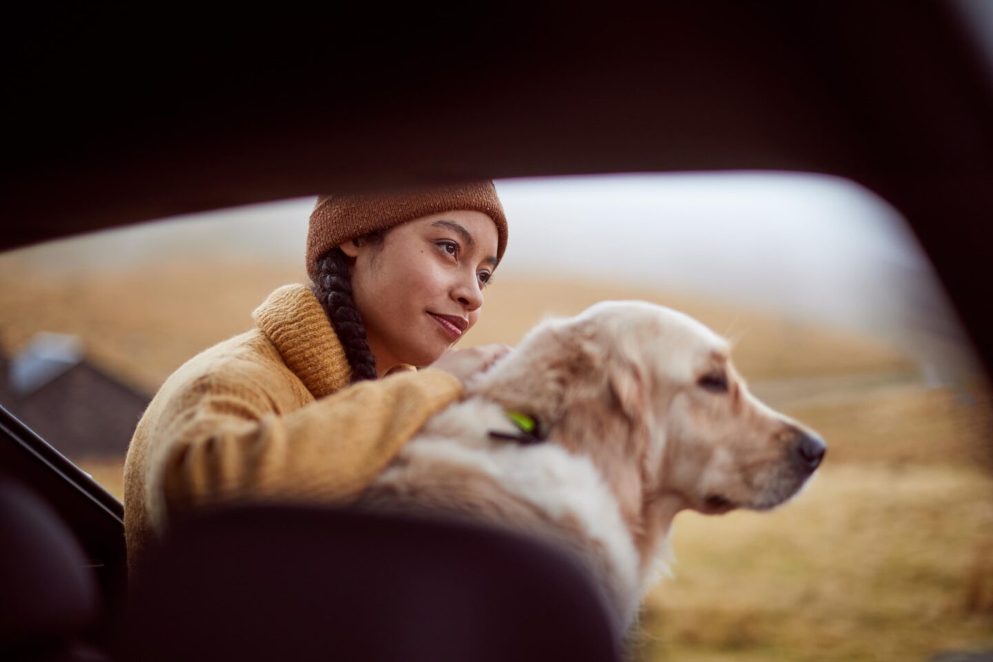 Girl with golden retriever in car