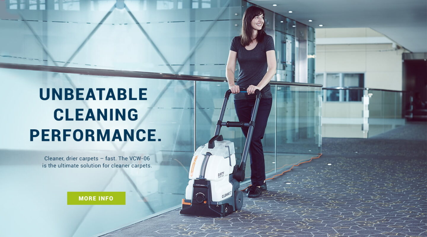 Cleaner using Vax commercial carpet washer in a corridor